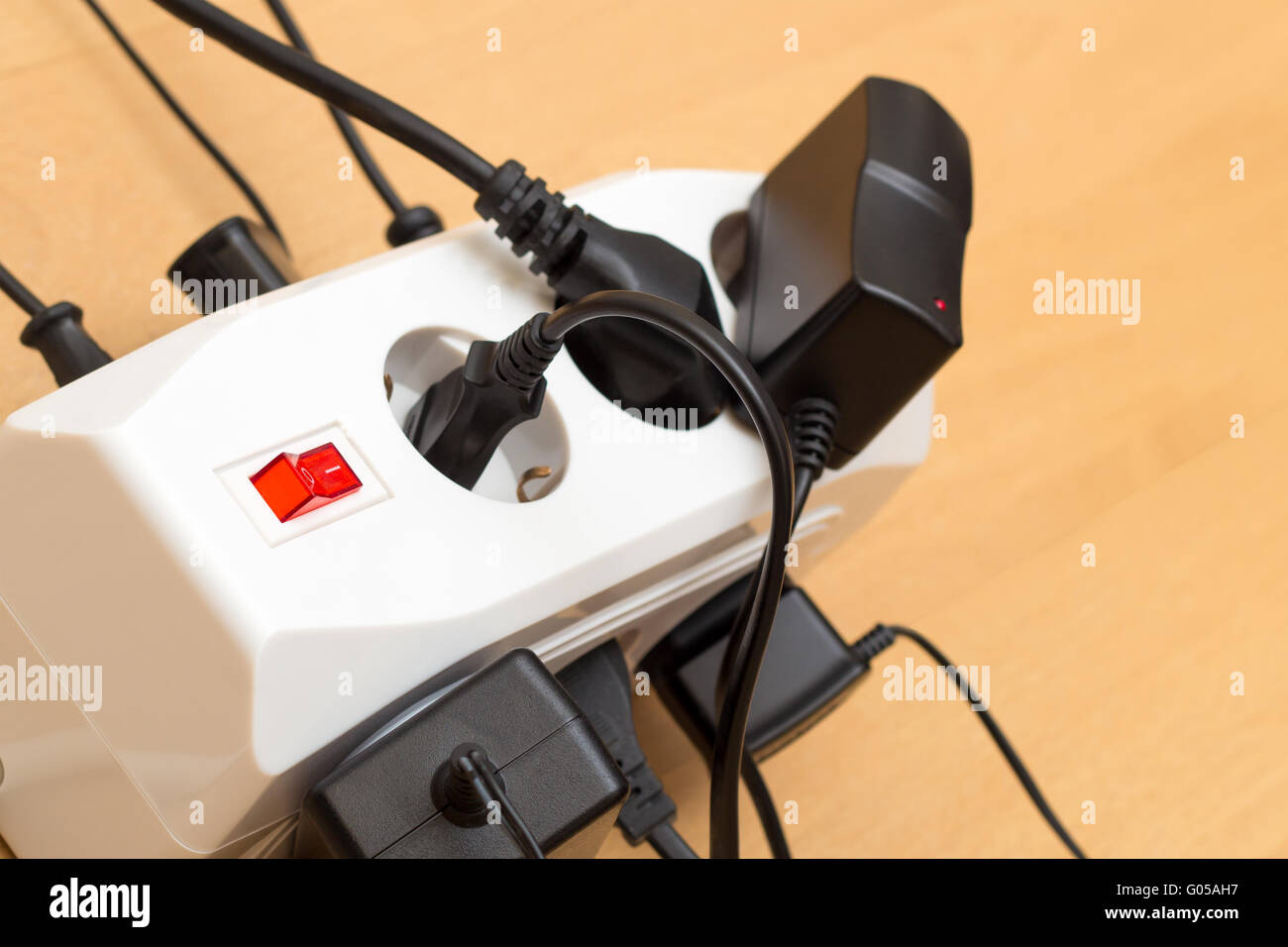Many plugs in a power strip - Stock Image