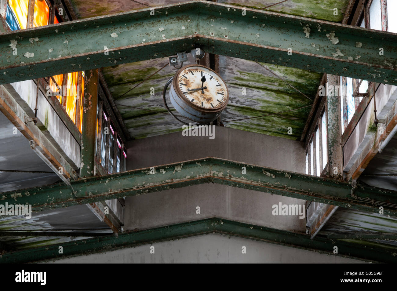 Clock in a dilapidated metal products factory - Stock Image