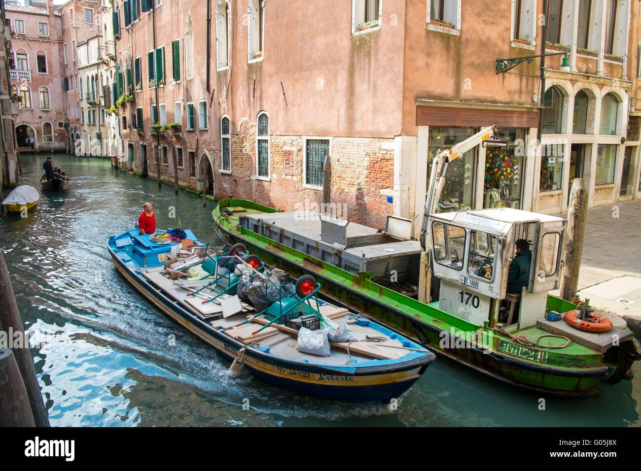 A builders canal boat passes a refuse barge on a venetian waterway, Venice, Italy, April - Stock Image