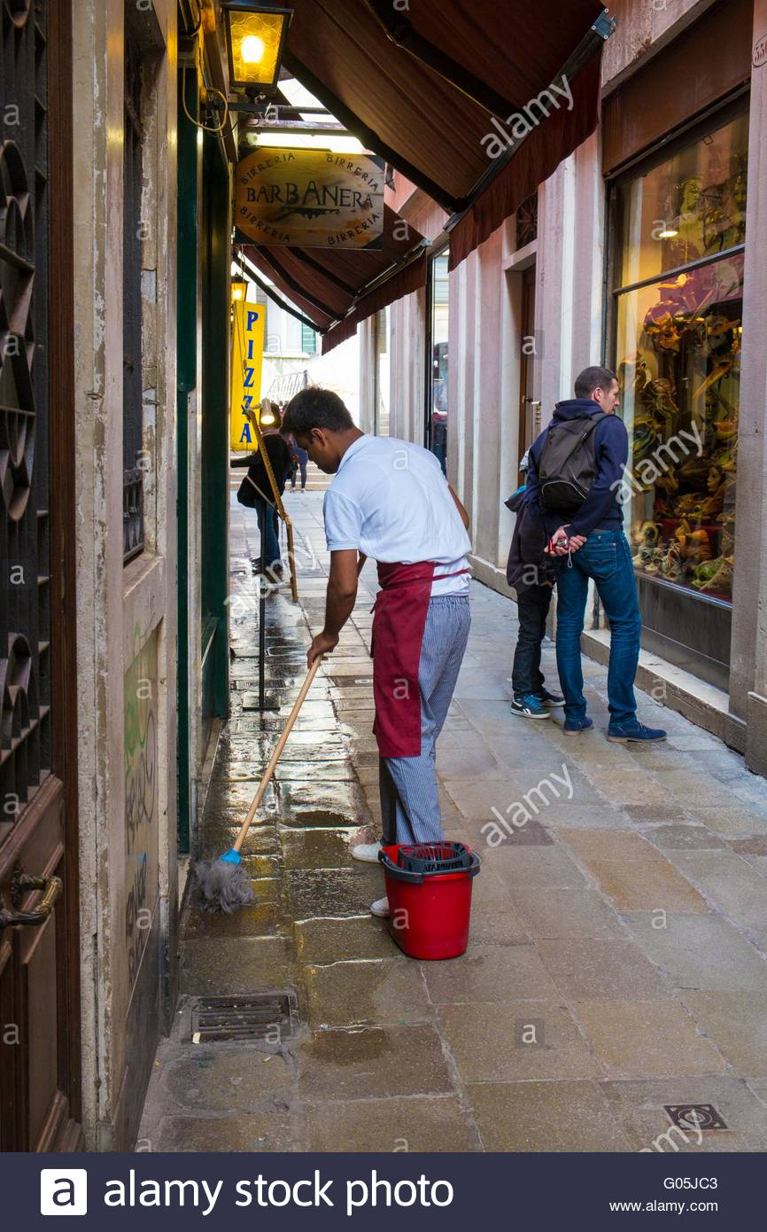 Resturant worker washing down pavement prior to opening, Venice, Italy, April - Stock Image