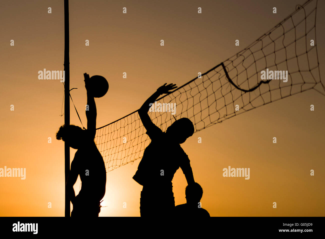 Volleyball playing people silhouettes with vollayball and the net. - Stock Image