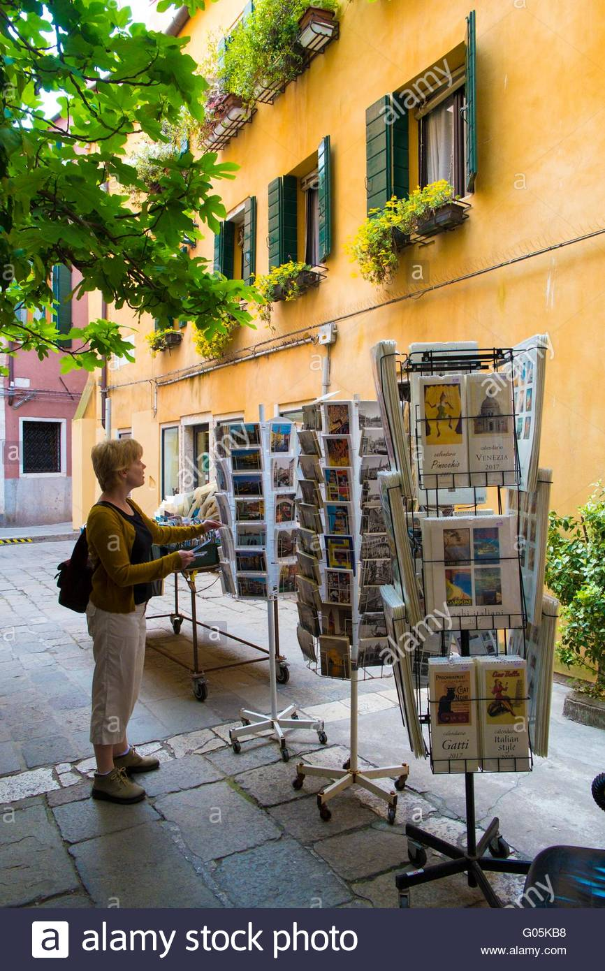 Woman selecting postcards, Venice, Italy, April - Stock Image
