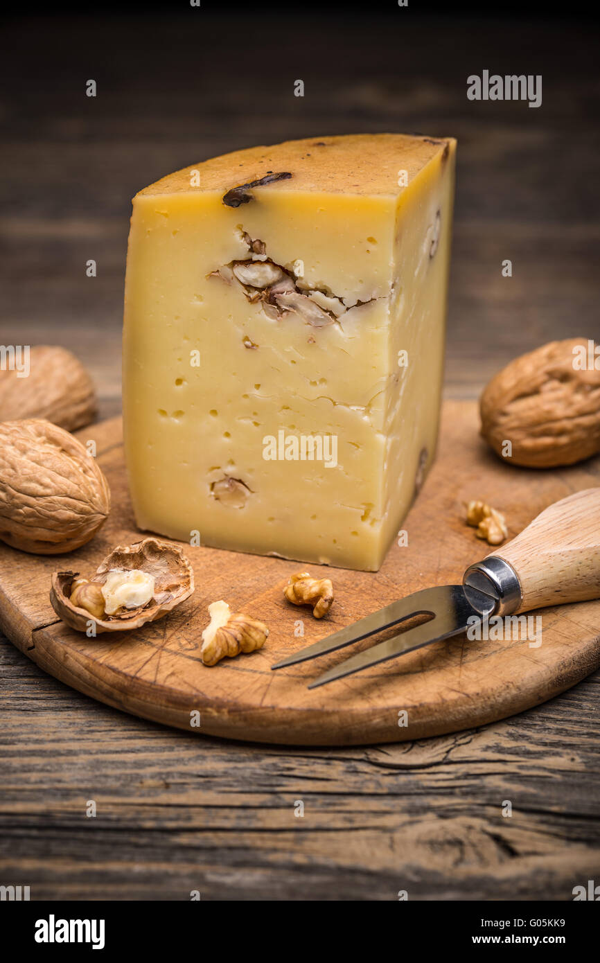 Artisan cheese with walnut on wooden cutting board - Stock Image