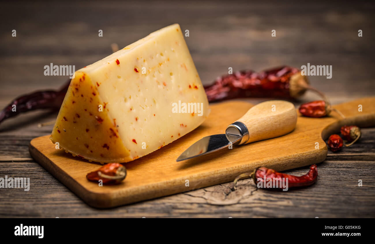 Piece of cheese with chilli on wooden board - Stock Image