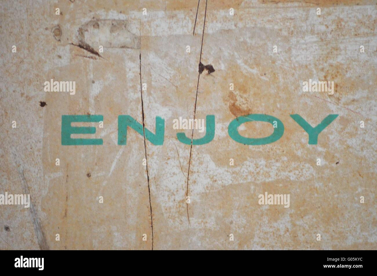 The word Enjoy written in turqoise on old metal - Stock Image
