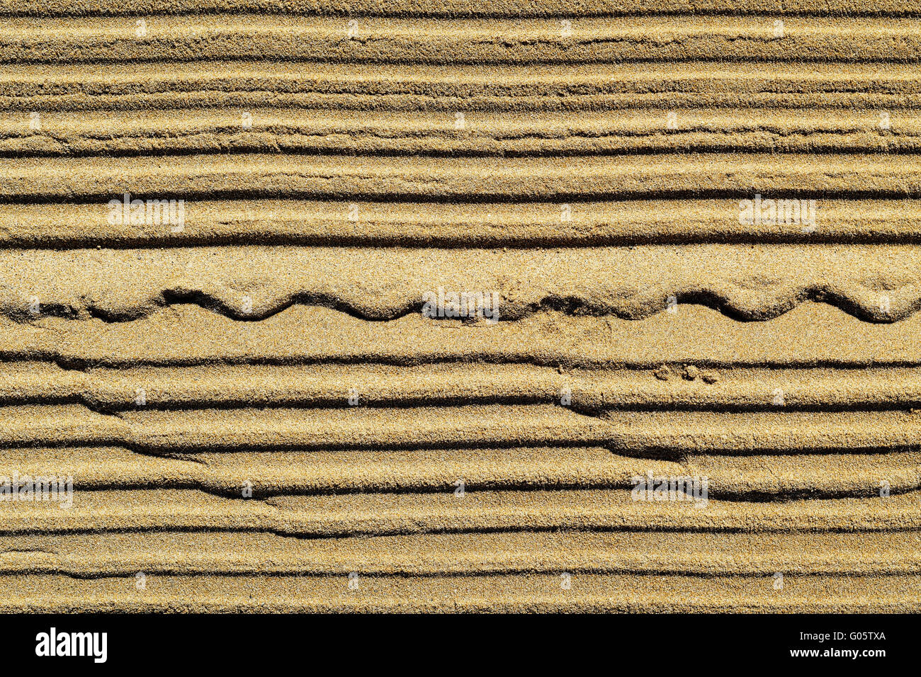 closeup of a striped pattern in brown sand - Stock Image