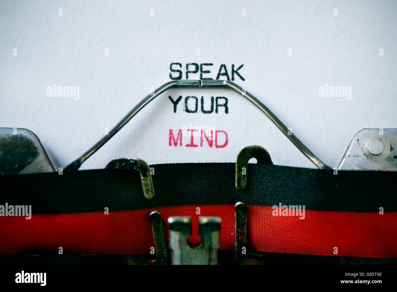 closeup of an old typewriter and the text speak your mind typewritten with it in a foil, with a vignette added - Stock Image