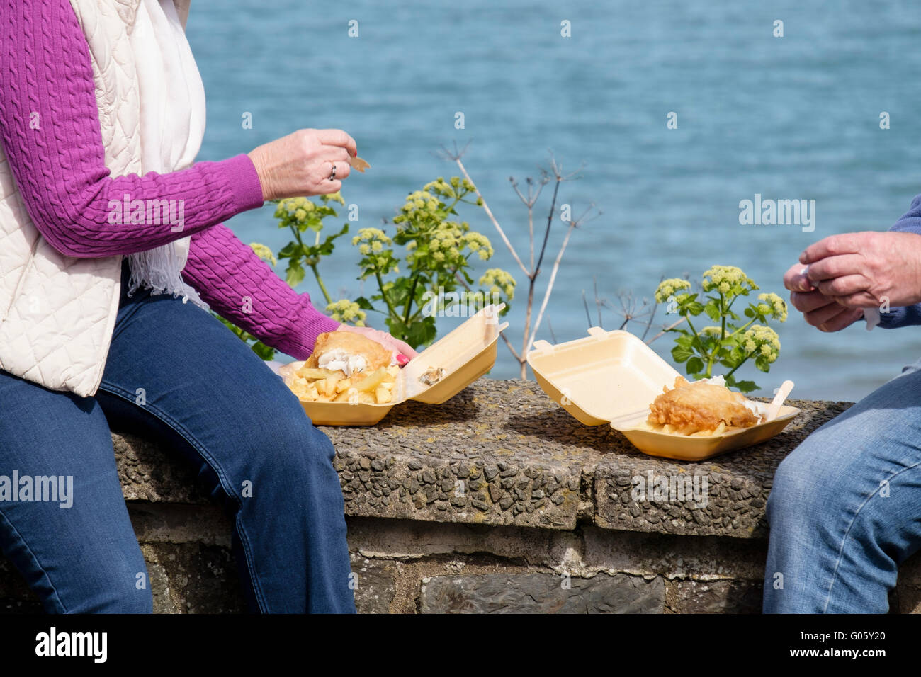 Two people holiday makers sitting on a sea wall eating takeaway fish and chips from polystyrene containers in seaside - Stock Image