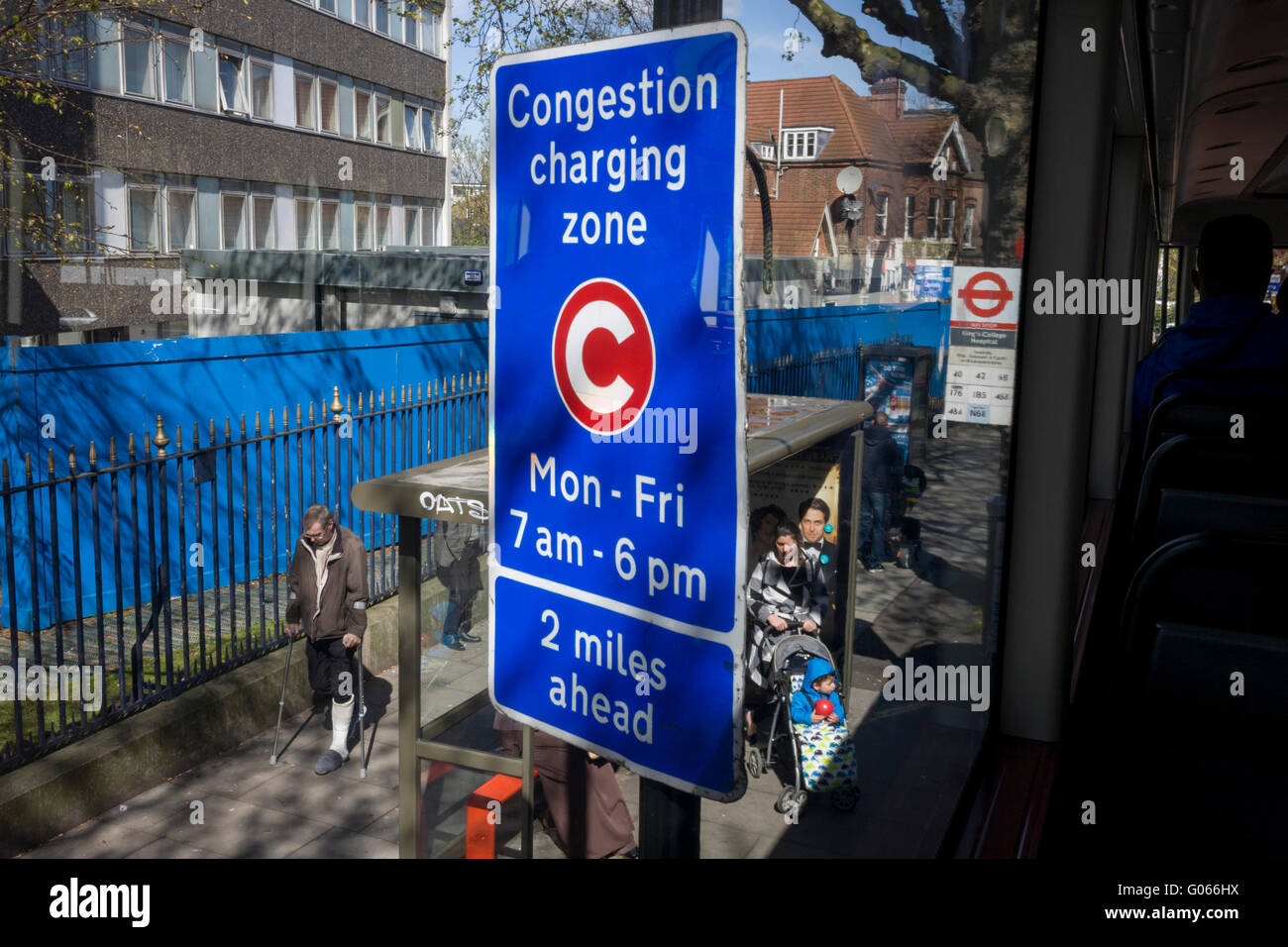 Aerial view of a bus stop and TFL Congestion Charging Zone sign, seen from the top deck of a London bus, outside - Stock Image