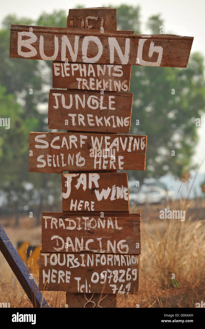 Bunong hilltribe sign advertising elephant & jungle trekking, scarf weaving & traditional dancing, Mondulkiri - Stock Image