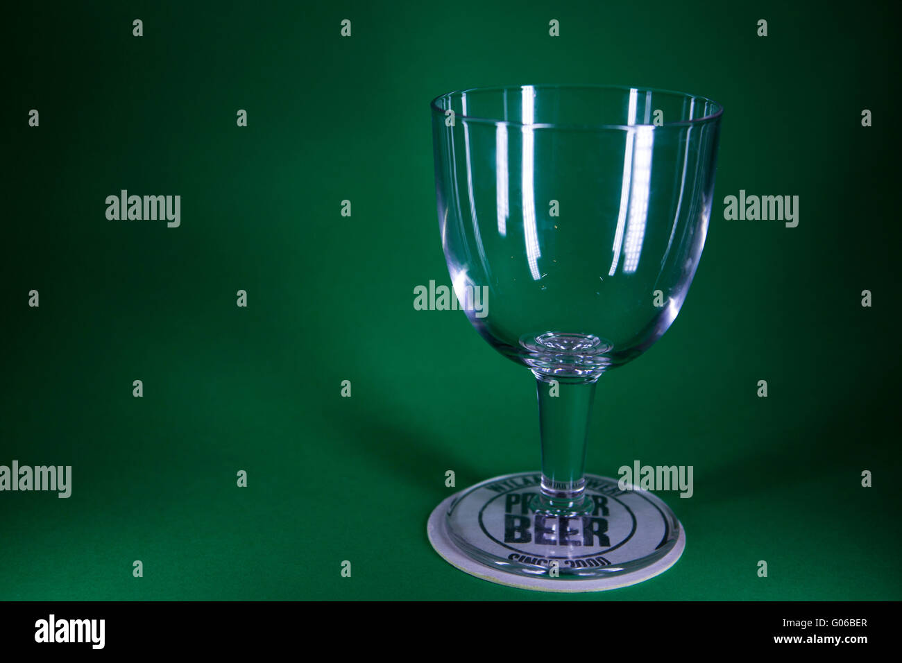 A beer glass stands on a beer mat. The scene has a green background. Stock Photo