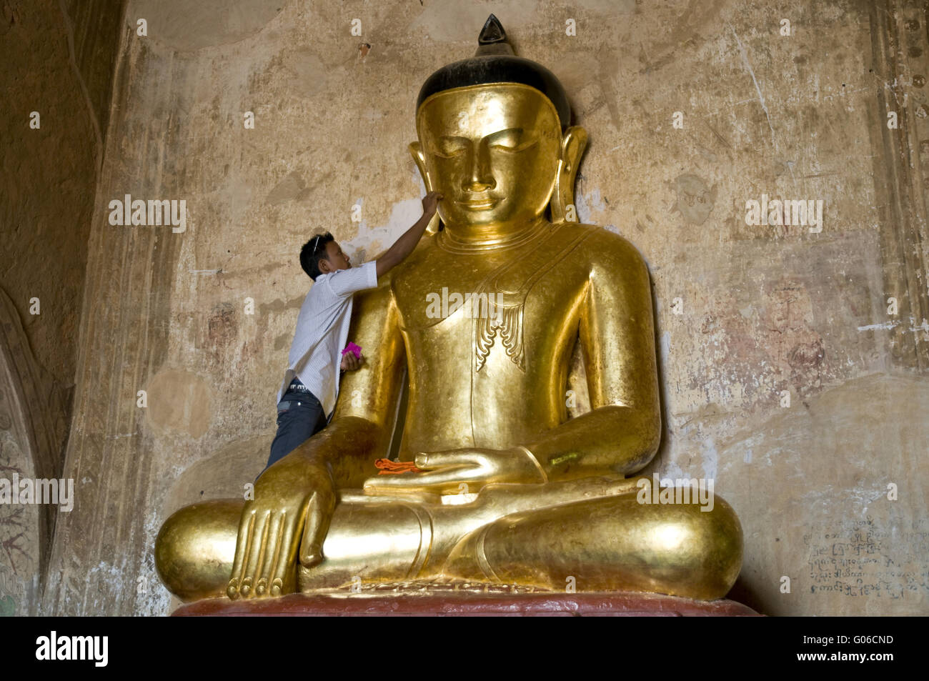 Man applies gold leaf to Buddha image, Burma Stock Photo