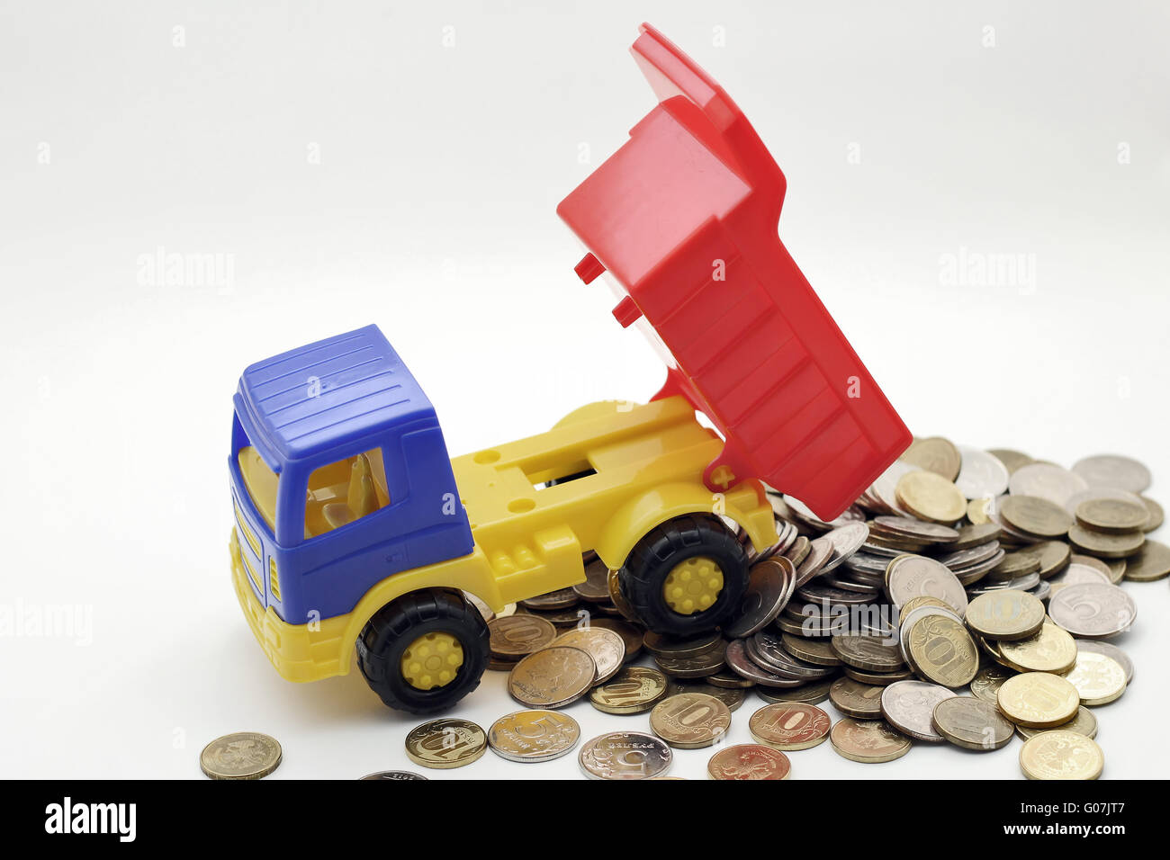 Toy truck transports coins. on white background - Stock Image