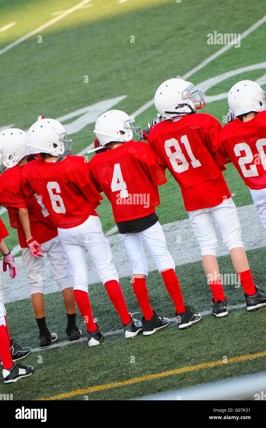 Young football players on sidelines - Stock Image