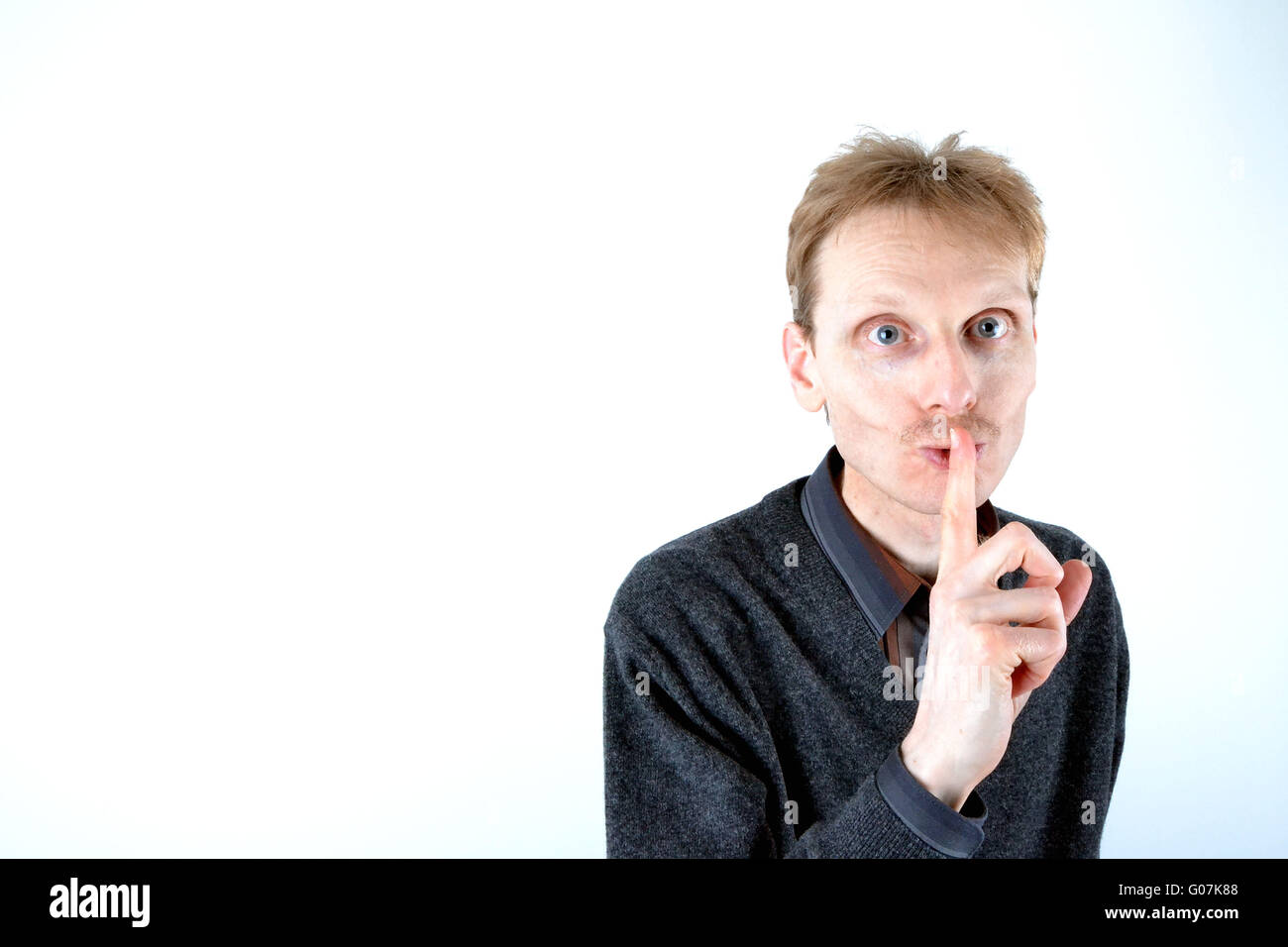 Blonde man who has his finger at the mouth Stock Photo