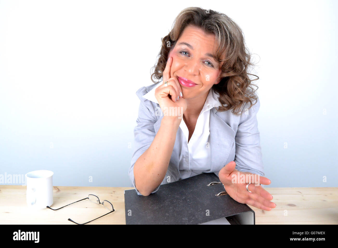 The happy woman sitting at the desk Stock Photo