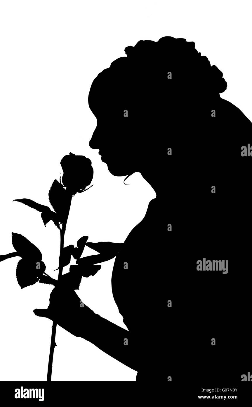 Silhouette of woman in wedding dress with rose - Stock Image