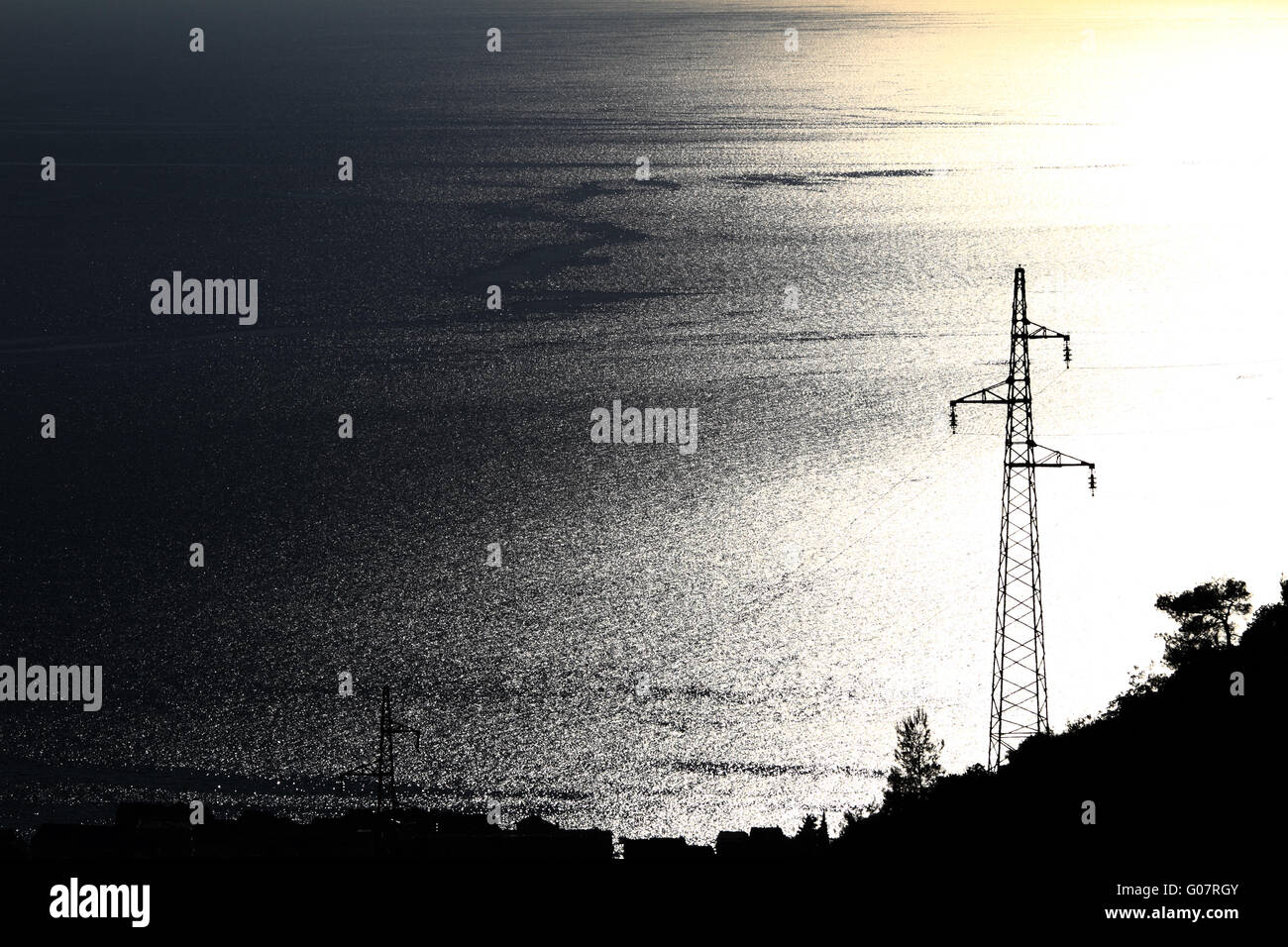 Electricity pylon with many cables on blue and yellow sea - Stock Image