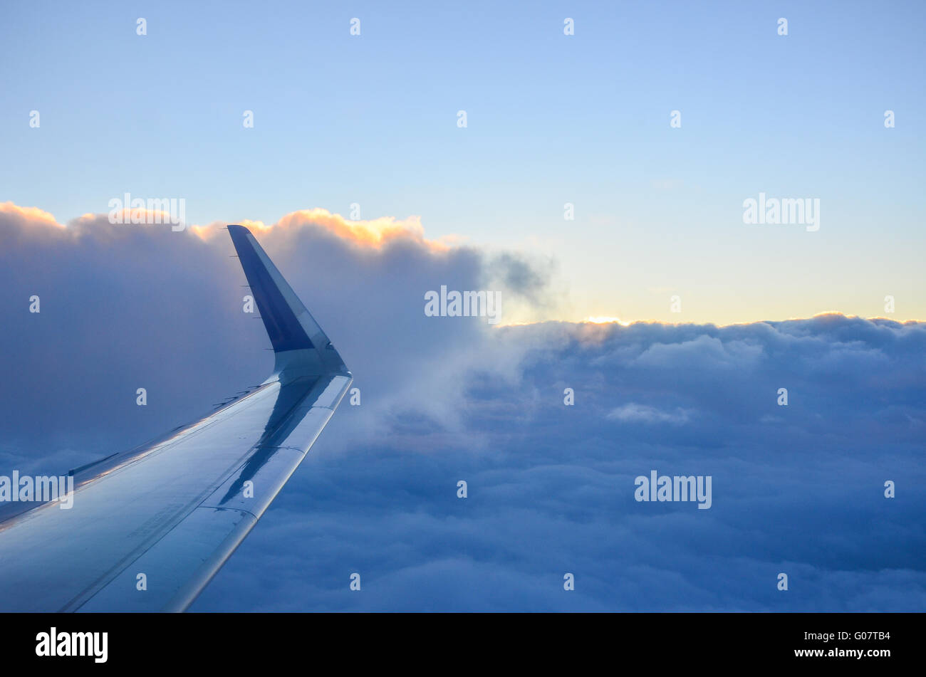 IndiGo Airlines flight window view of clouds with sunset orange lining. - Stock Image