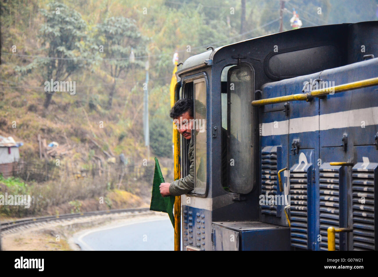 Loco pilot of the Darjeeling Himalayan Railway Toy Train showing green flag, looking behind. - Stock Image