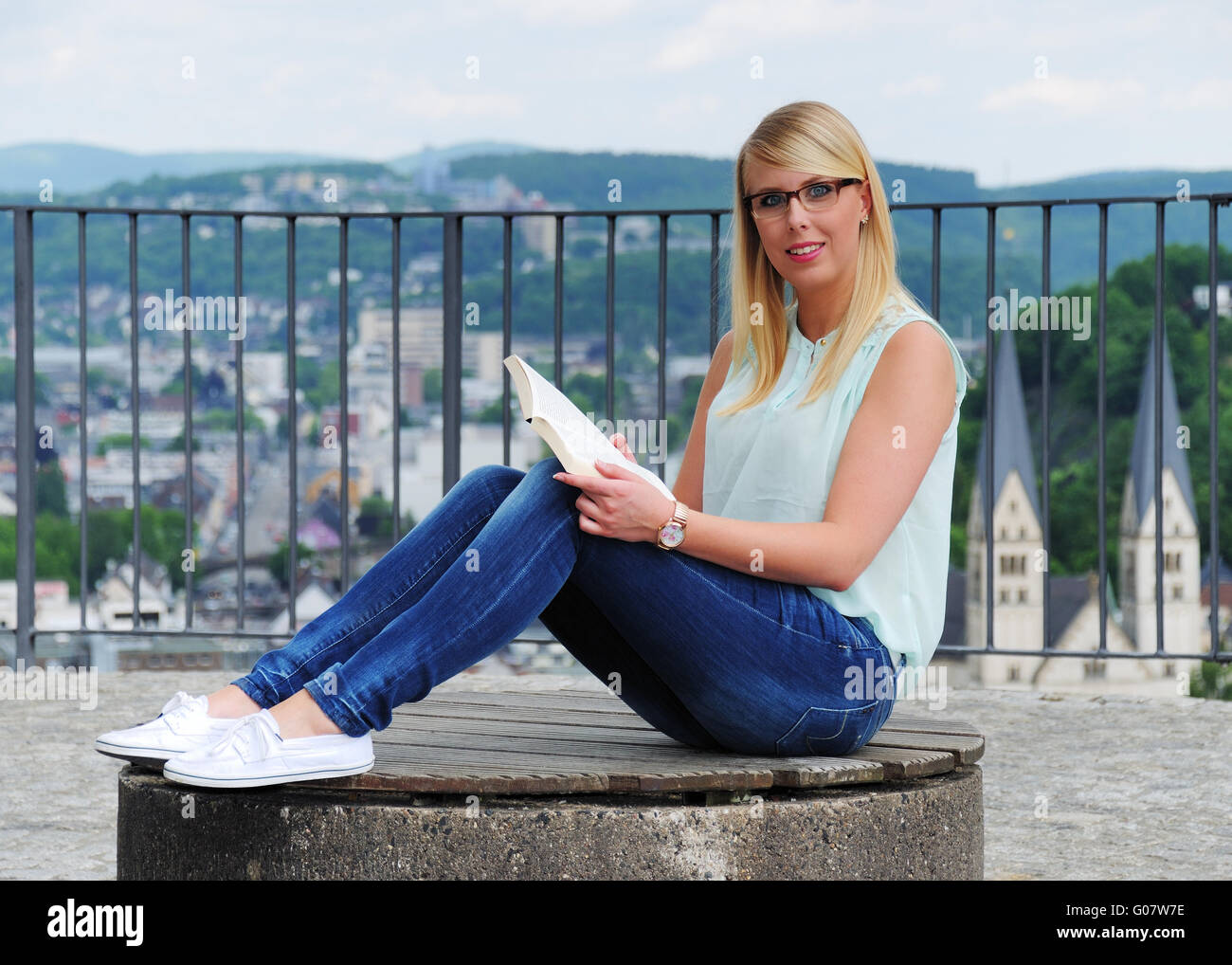 young woman is sitting and reading in Siegen - Stock Image