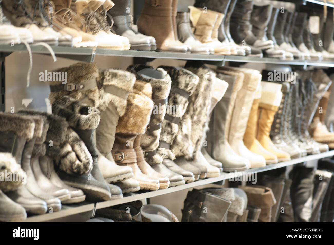 Outlet Center shelf with women's winter boots - Stock Image