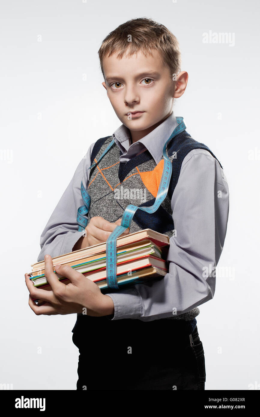 Little boy measures books by a meter tape. Looks i Stock Photo