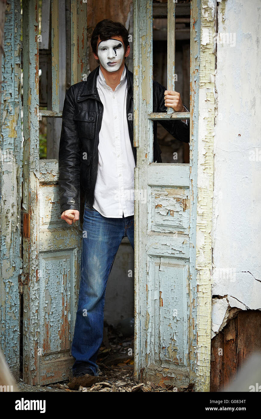 Guy mime against the old wooden door. - Stock Image