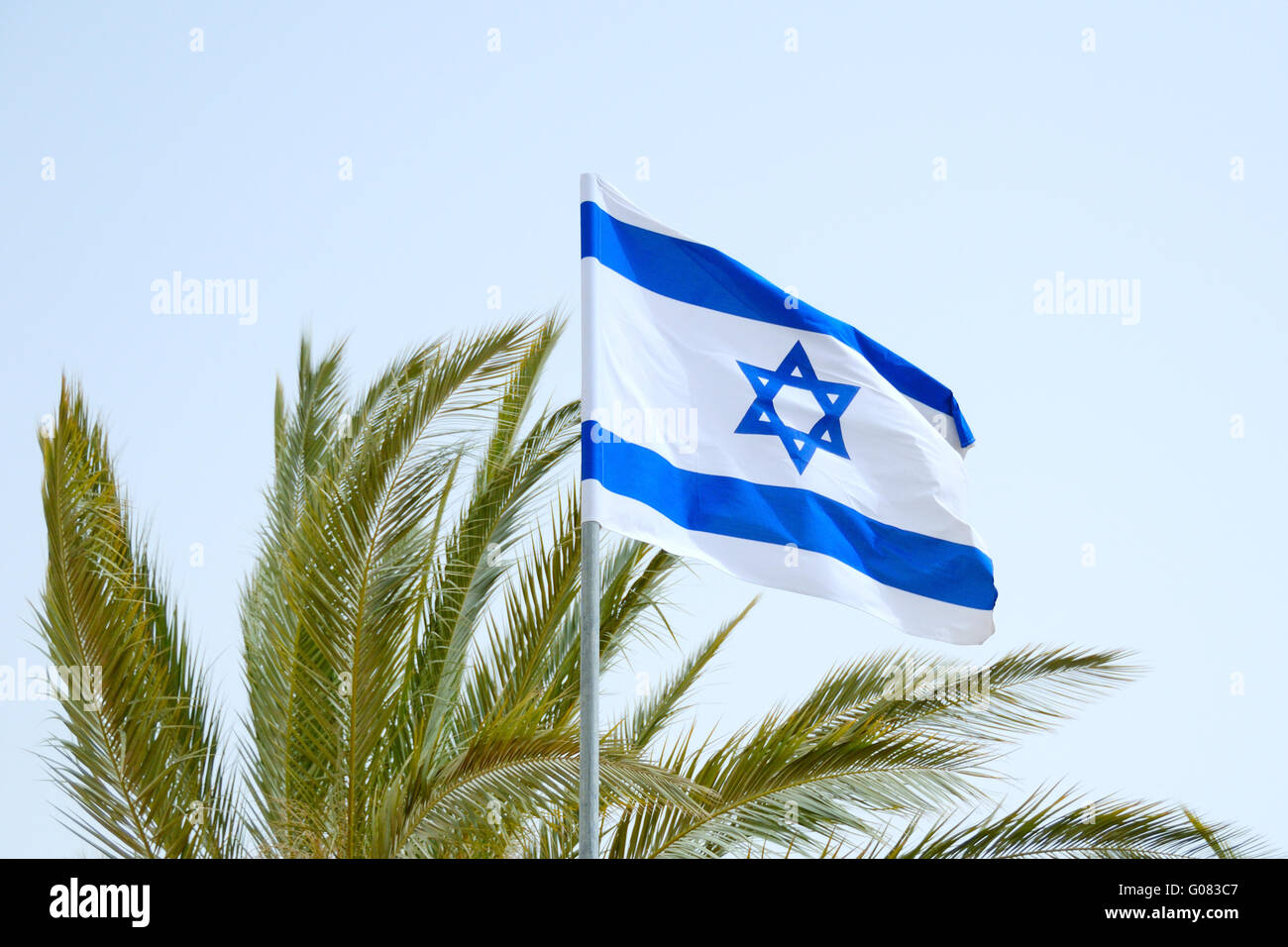Israel's flag float on the wind against a sky. - Stock Image