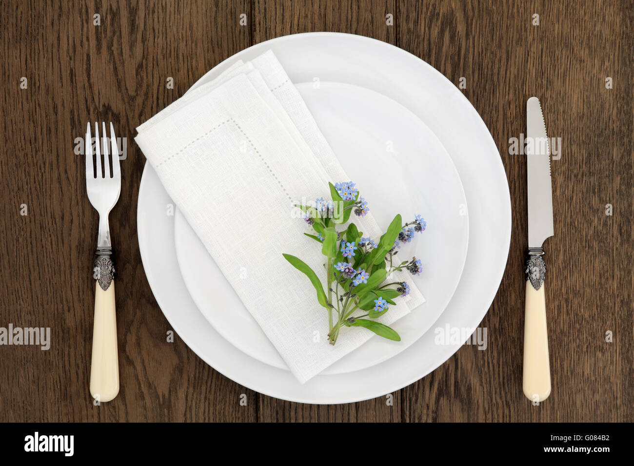 Dinner table place setting with forget me not flowers white round porcelain dishes and linen napkin with antique cutlery. & Dinner table place setting with forget me not flowers white round ...