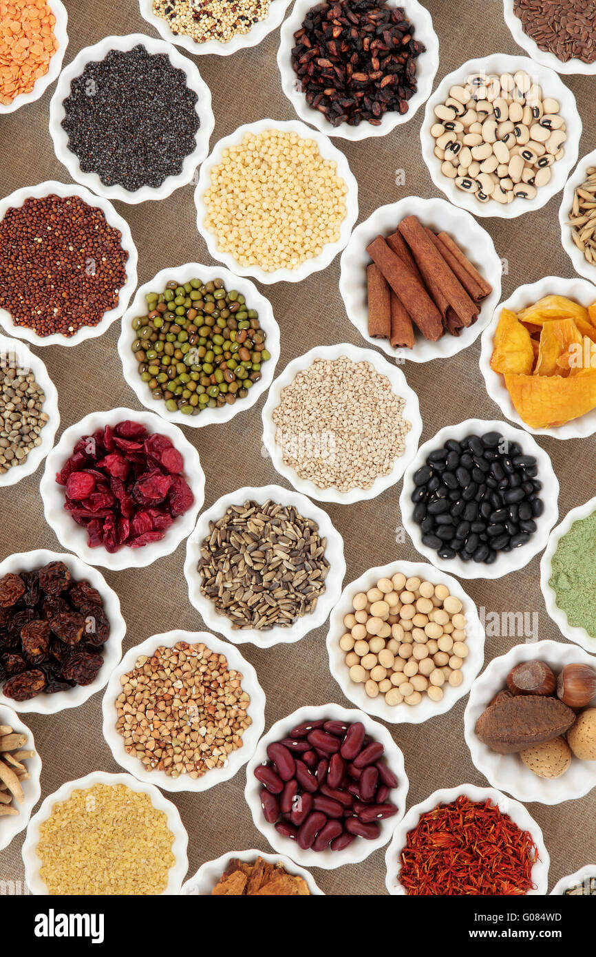 Dried health food in china bowls over hessian background. Foods high in minerals vitamins and antioxidants. - Stock Image