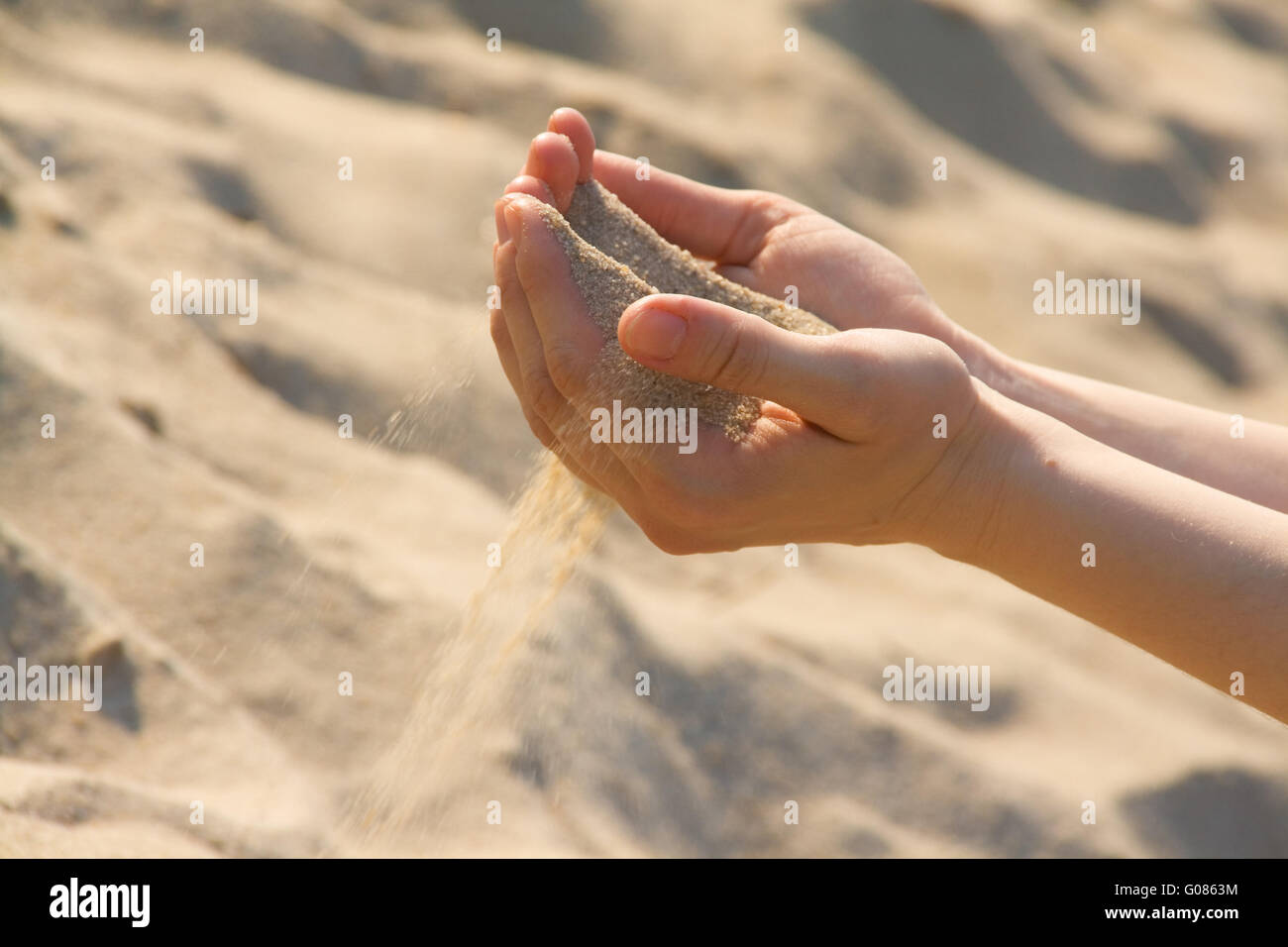Sands pour through fingers. temporariness of life Stock Photo
