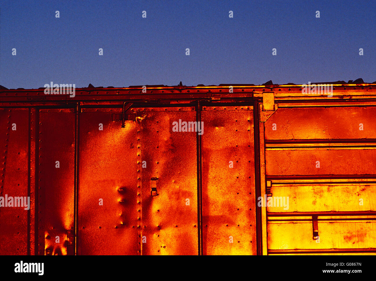 Setting sun reflects off of freight train car - Stock Image