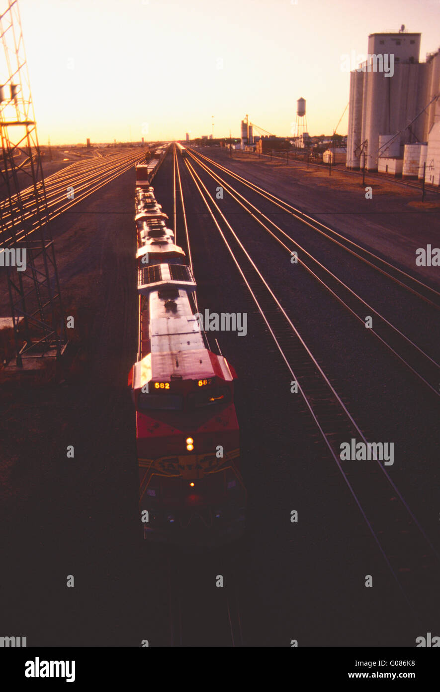 Locomotive in large industrial rail yard at sunset; Clovis; New Mexico; USA - Stock Image