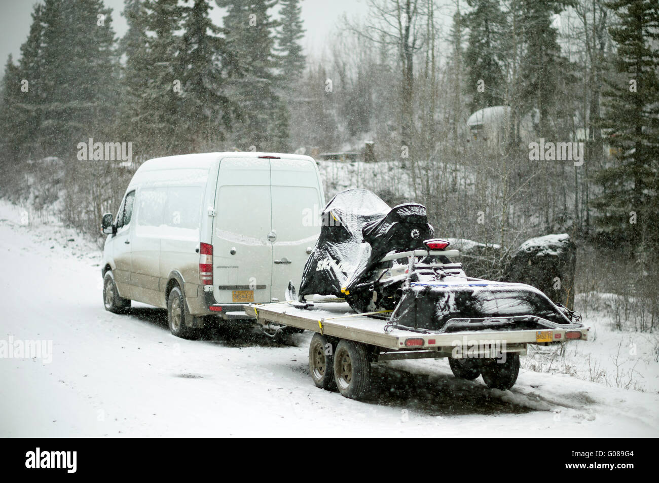 Winter driving in Alaska. Freightliner Sprinter Cargo Van pulling the Ski Doo Expedition snow machine on the trailer - Stock Image