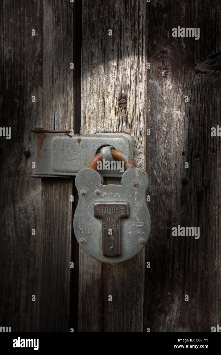 Moody lighting shed Squire padlock on rustic weathered wood background - Stock Image