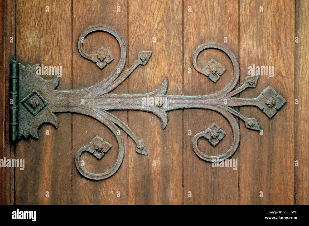 Close-up Of An Ornamental Iron Hinge On An Old Wooden Door - Stock Image