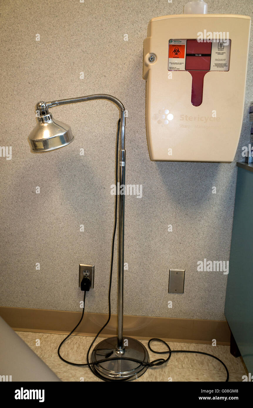 Doctor's office goose neck examination light and Stericycle for safely collecting used needles. Minneapolis - Stock Image