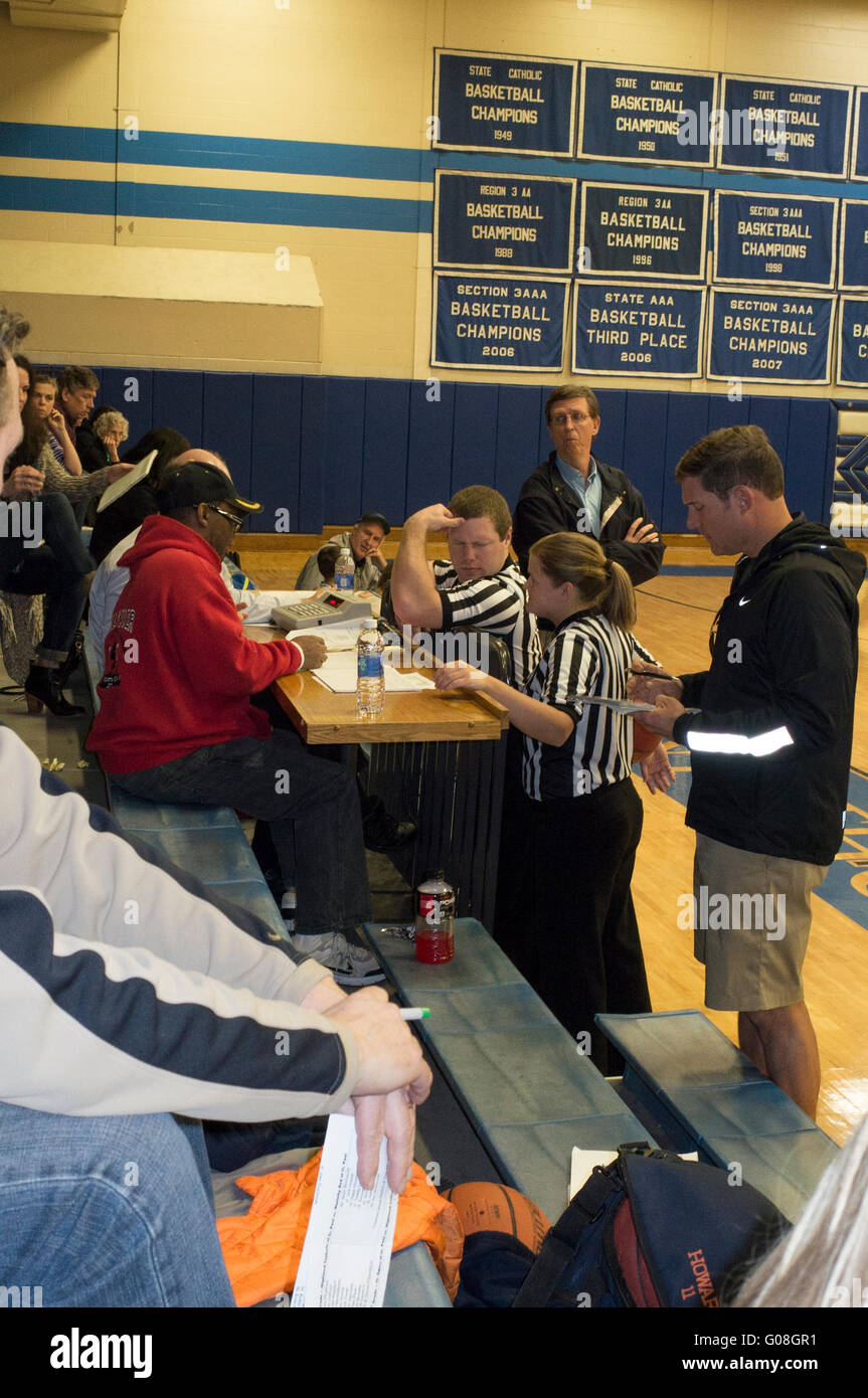 Man and woman basketball referees checking in at the  timer and score keeper's table. Mendota Heights Minnesota - Stock Image
