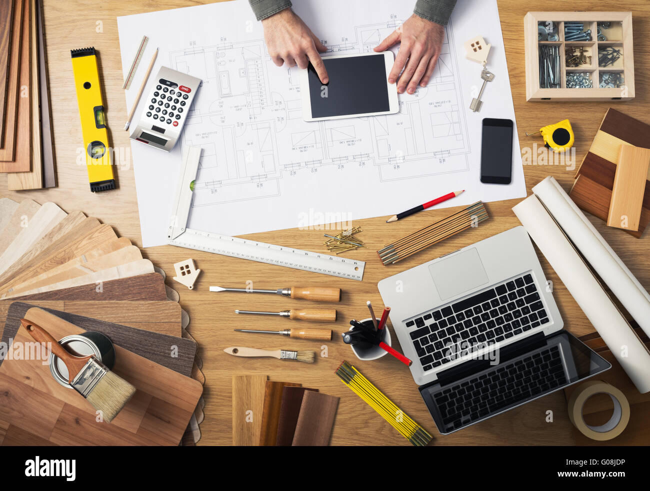 Construction engineer and architect's desk with house projects, laptop, tools and wood swatches top view, male - Stock Image