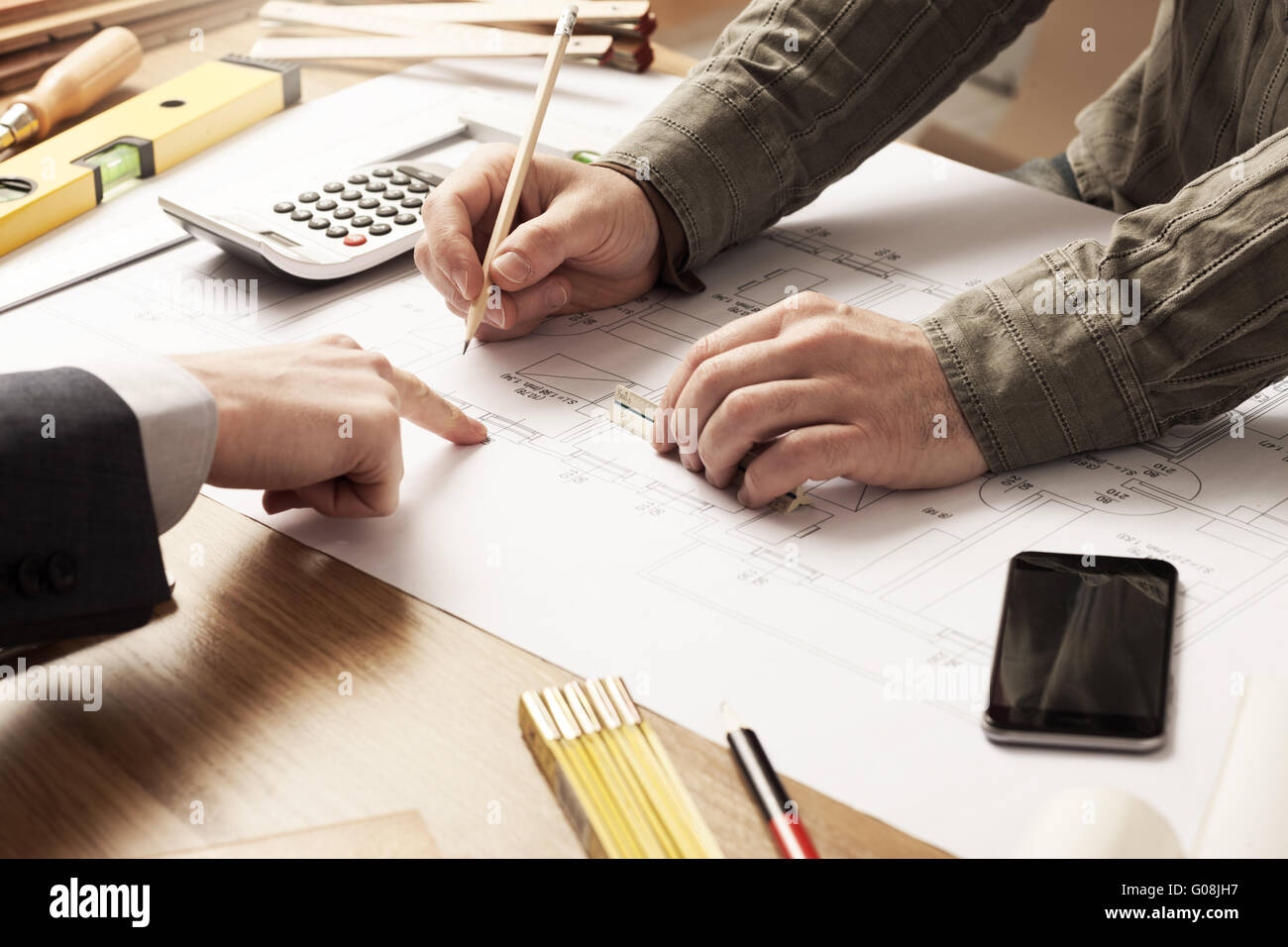 Businessman and construction engineer working together, the customer is pointing on the project on the desk - Stock Image