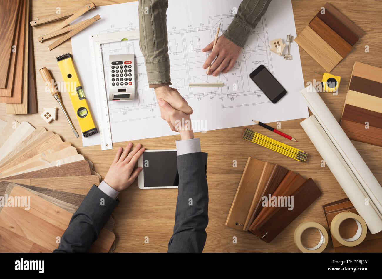Architect and customer businessman shaking hands top view, desktop with building project, tools and wood swatches - Stock Image