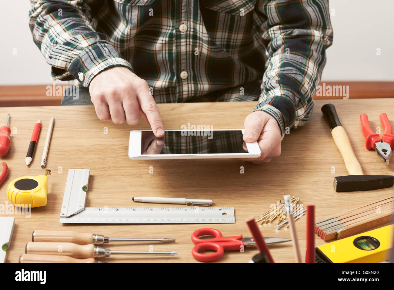 Man working on a DIY project at home with a digital tablet, carpentry and construction tools on a work table, hands - Stock Image