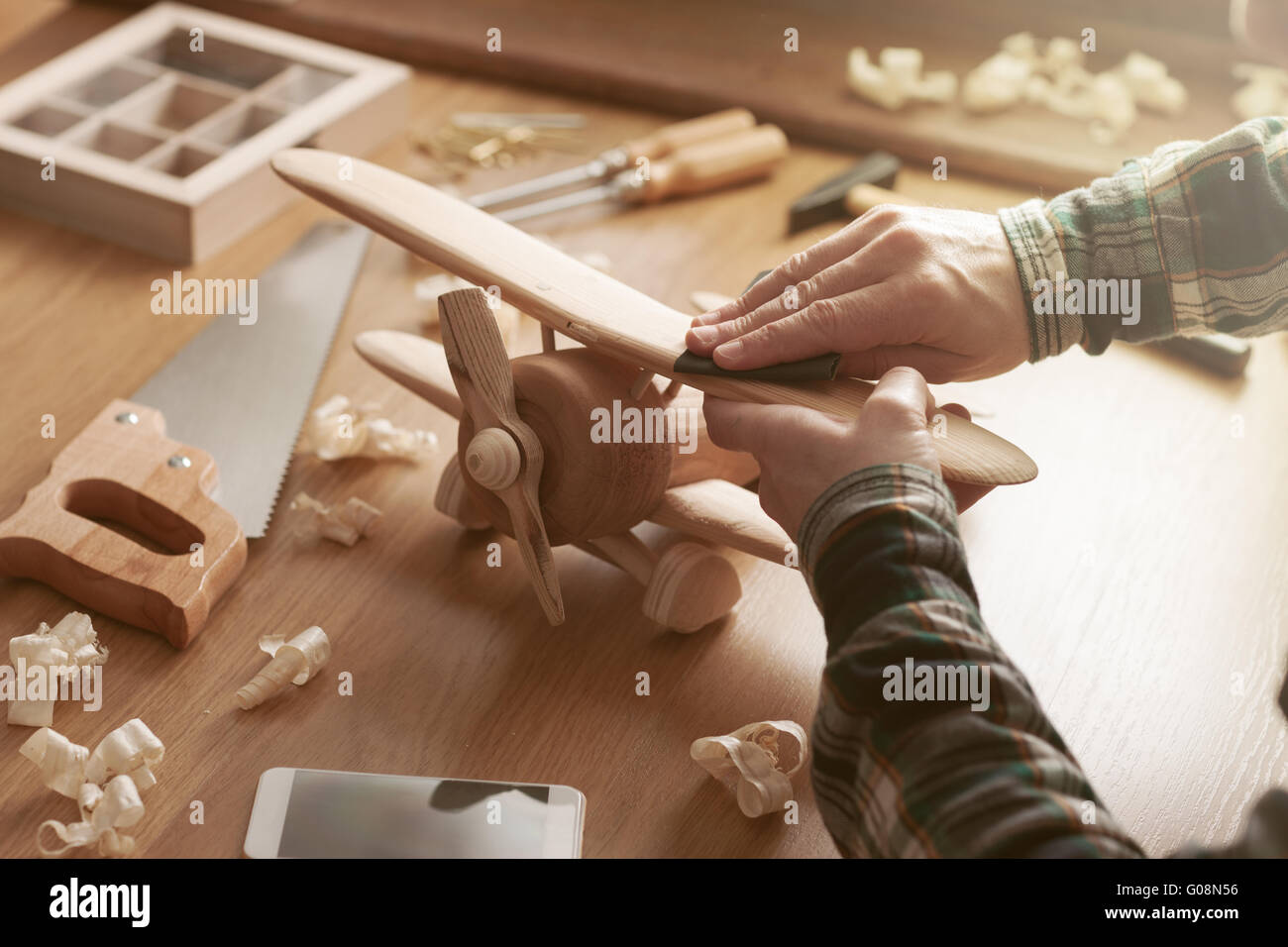 Craftsman smoothing a wooden toy surface with sandpaper, tools and wood shavings all around, hands close up Stock Photo