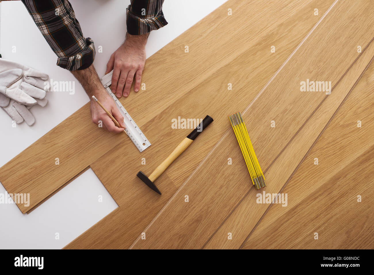 Carpenter Installing A Wooden Flooring And Measuring With A