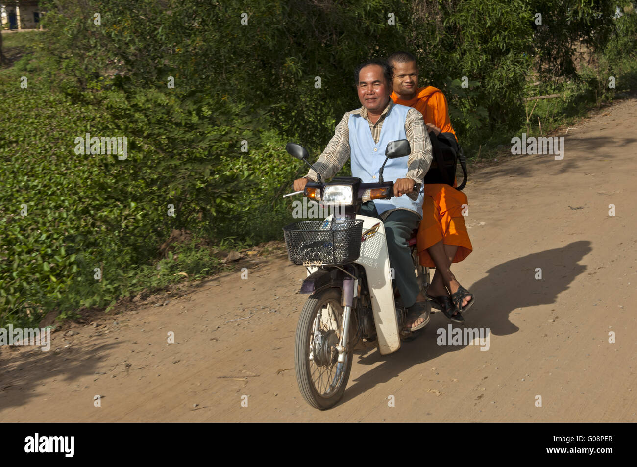 Buddhist monk riding as passenger on a motor-bike Stock Photo