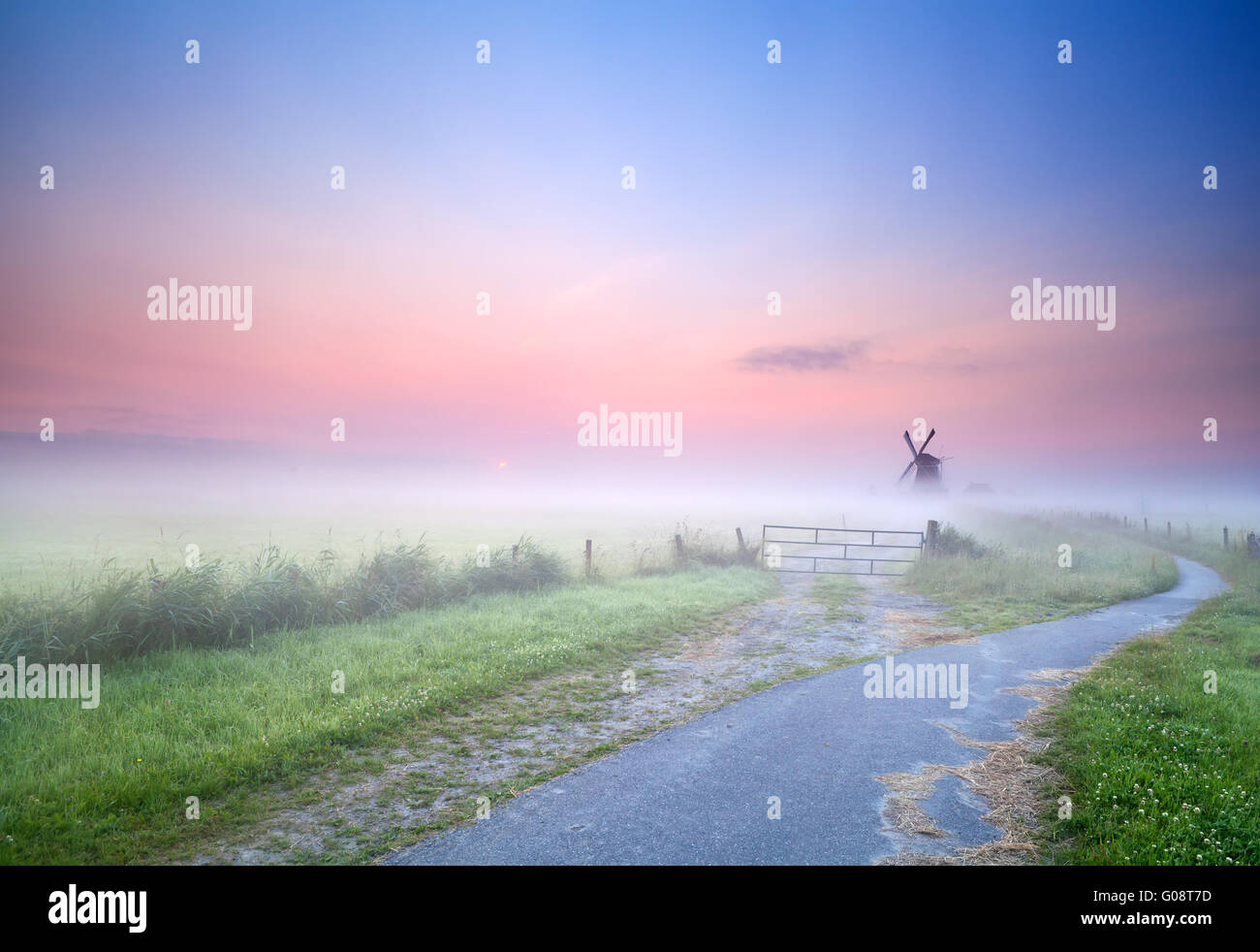 way to windmill in morning fog - Stock Image