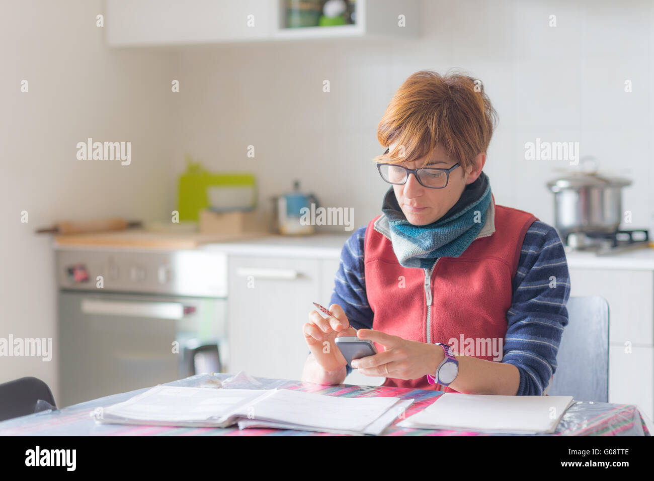 Woman with eyeglasses sitting at table, reading and handwriting paperwork and documents. Selective focus, home interiors. - Stock Image