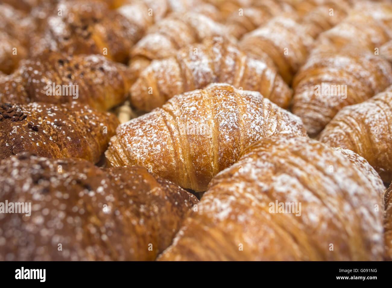 Freshly baked italian croissants (cornetti) background. Low depth of field - Stock Image