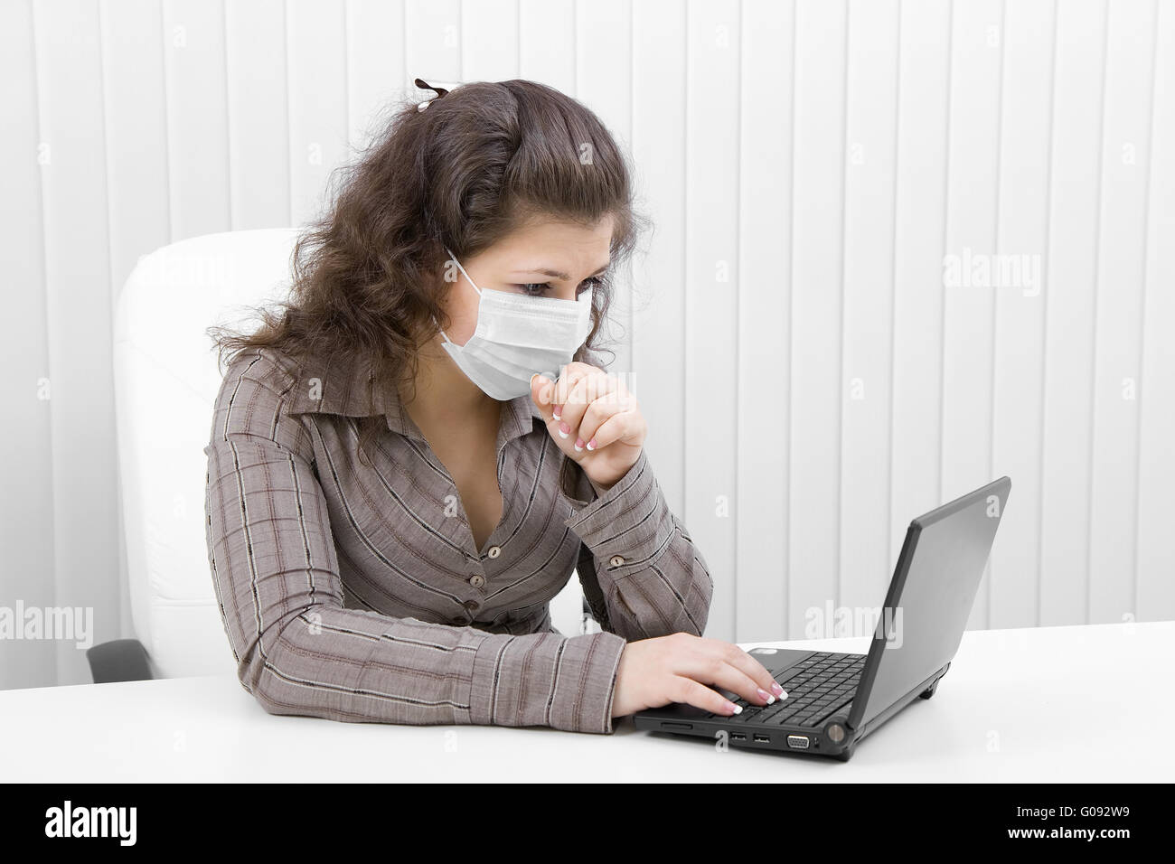 The young woman in medical mask with the laptop - Stock Image